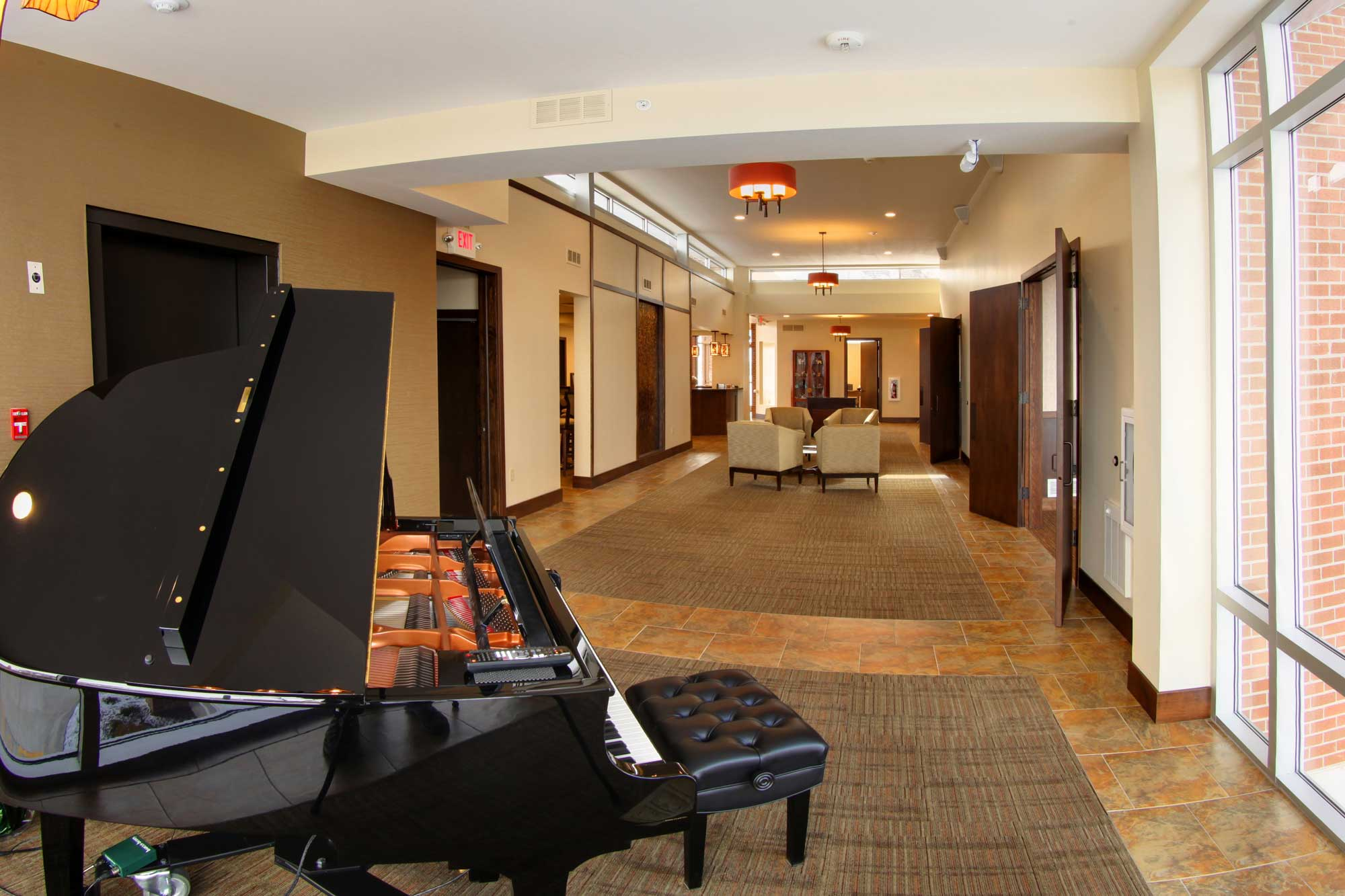 Feature of Trimble point funeral home showing a long hallway with the grand piano in the forefront